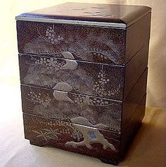 """Maki-e Jubako Stacking Bento Box c.1920 -- Antique Japanese four-tiered stacking bento delicacy food box for outings to kabuki or cherry blossom viewing. The multi-layered lacquer is decorated w/ gold maki-e or raised gold paintings w/ inlay pearl insets. (9½"""" x 7¼"""")"""
