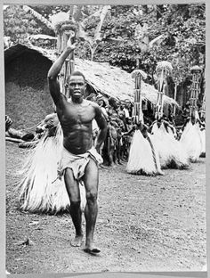 An attendant leading a group of young Igbo male initiates participating in the masquerade performed by Isiji (junior age-grade members), dancing in a single file in a circle. The Isiji are wearing wearing tall conical headdresses, palm...