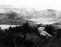 A marine infantryman keeps cover as he looks over the Han river valley near Seoul four days after the flanking movement against Inchon. (U.S. Navy photo.)