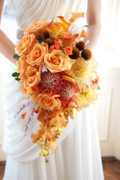 Stunning orange cascade with roses, calla lilies, protea, and mokara orchids.