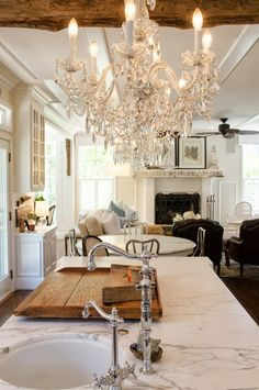 Love everything -- mix of old (wood beams and dark chairs), elegance (chandelier and marble countertop) and homey (pillows and the couch).