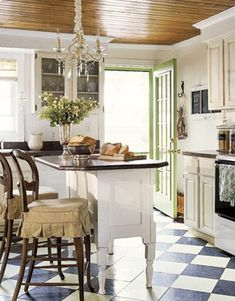 Adore this kitchen. Plank ceiling. Chandi. Bar stool skirted pads. Green door and frame (the best part!). Black and white floor.  And so on...