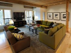tapis gris, canapé d'angle vert olive et fauteuils marron dans le salon élégant