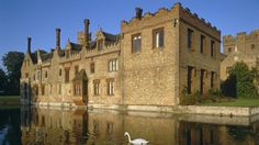 Residents of Oxburgh Hall must have had the perfect opportunity for playing hide and seek! The hall boasts a priest hole and secret doors which today's visitors to the hall can investigate. The moat at Oxburgh Hall with a swan in the foreground © NTPL/Ray Hallett