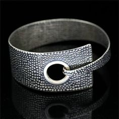 This textured geometric bangle has been designed and hand crafted by Charlie High. The contrast of textures together with the geometric shapes contrast