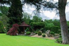Celkový pohled na pravou stranu zahrady s altánem, v pozadí lužní les.