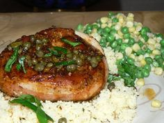 Rib Eye Pork Chop Wrapped in Bacon, Topped with Beer and Caper Pan Sauce. Parmesan Couscous, Baby Peas and Sweet Corn.