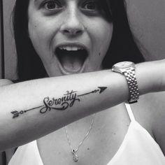 Pequeño tatuaje de una flecha que cruza la palabra 'Serenity' (en español 'Serenidad') en el antebrazo de Eden. - Pequeños Tatuajes