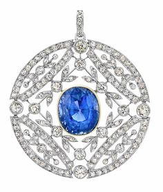 Belle Epoque Platinum, Gold, Sapphire and Diamond Pendant with Chain   The circular openwork pendant with a garland motif centering one oval sapphire approximately 13.50 cts., set throughout with 112 old-mine cut diamonds approximately 3.70 cts., accented by rose-cut diamonds, approximately 12 dwt.