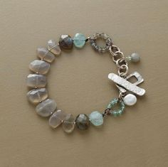 """calm before the storm bracelet  Clouds of moonstone and labradorite burst into a flurry of design elements: gemstone ringlets, danglers and a cultured coin pearl near a prominent sterling silver toggle clasp. Handmade exclusive. 7-1/2""""L."""