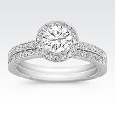 This beautiful vintage inspired wedding set features one round halo set diamond, at approximately .70 carat.  This dazzling gem is surrounded by 56 round diamonds, at approximately .36 carat TW.  Hand-matched for maximum fire and brilliance, these stones are set in quality 14 karat white gold and the total carat weight is approximately 1.06 carats.