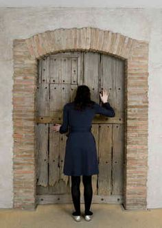 Marcel Duchamp, Étant donnés, Philadelphia Museum of Art / A visitor looks through two holes in a wooden door to Étant donnés, the Marcel Duchamp masterpiece behind it and the subject of a new show at the Philadelphia Museum of Art. Image via the Philadelphia Inquirer.