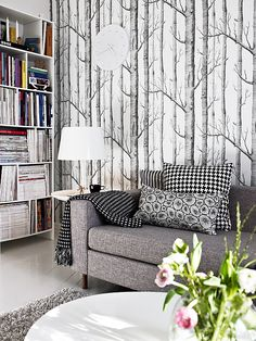 I love the white floor, bookcases & coffee table! I also love this wallpaper but I don't know if I would ever use it in a room, especially in a starter house. I do like more color in a room, this is all to gray.