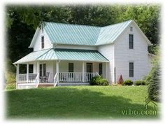 old, white farmhouse with green roof