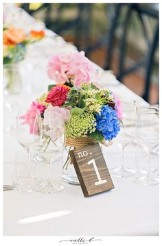 Reception centrepieces in glass jars with bright flowers including hydrangea