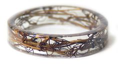 Designer Sarah Smith at Modern Flower Child (previously) continues to experiment with embedding all manner of plantlife into her handmade resin bracelets. Dried ferns, flowers, bark, and even peacock feathers are frozen in time inside these clear time capsules, a process that takes up to three weeks