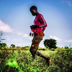 A young man harvests tomatoes with his radio hanging around his neck, listening to love songs, Ghana. Photo by Nana Kofi Acquah