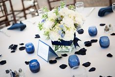 The centerpieces were designed in square glass cubes we used white carnations, white hydrangea, and lots of blue delphinium. We bound the vases with navy blue satin ribbon.