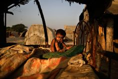Islamabad, Pakistan: A displaced child tries to remove flies from her face at a makeshift home in a slum