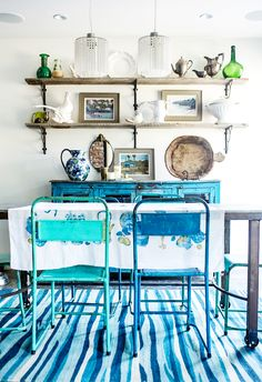 French-inspired, rustic dining space with art displayed on wood shelves, metal colorful dining chairs, and blue credenza