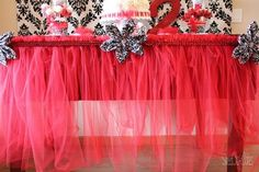 Tulle table skirt: 10 yards of tulle, tablecloth, ribbon, pins.    Laydown table cloth on table, fold tulle in half, gather tulle and pinn to tablecloth (allow excess of 2-3 inches of tulle to stick up on top), gather and pin and repeat. After you go all the way around, take ribbon and pin to tablecloth (hides needles).