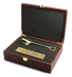 "NFPB-02  Wood Box with Gold Shovel	 An elegant Rosewood-finished Presentation Box with 8"" 3-D Die-cast Gold-plated Shovel, nestled in a custom-cut foam insert. Personalization is available on a laser-engraved or printed plate.  Promotional ground breaking ceremony gifts, awards & ideas for Groundbreaking Ceremonies & Events.  www.groundbreaking-awards.com  401-841-5646  #groundbreaking #groundbreakingceremony #groundbreakingshovels #shovels #ceremonialshovels #largeshovels"