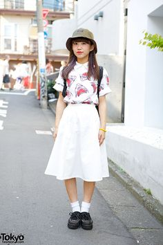 18-year-old Manami on the street in Harajuku wearing a shark print t-shirt with a WEGO skirt, an X-Girl bucket hat, and creepers from the fl...