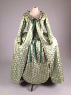 * Robe d'intérieur ou de grossesse, vers 1785-1790. Satin façonné vert tendre orné d'un bouquet de feuilles de chêne liées par un cordon à gland. Corset intérieur à nouer sur le devant et recouvert des deux pans du manteau au dos baleiné à l'an-glaise. Robe «flottante» à manches longues boutonnées, dé-colleté orné d'un ruché de la même étoffe et liens de resserrage en taffetas vert sur le devant. Doublure de Rouennerie en soie ou coton (dos à l'anglaise modifié au niveau des épaules)