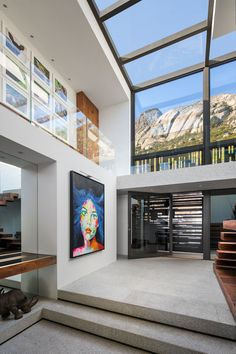 Stepping inside this modern house, double-height ceilings and windows that wrap around from the wall to the ceiling create a sense of openness and a dramatic entryway.