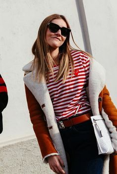 A red striped shirt from Comme des Garçons PLAY, worn with blue jeans, an orange belt, and a shearling jacket
