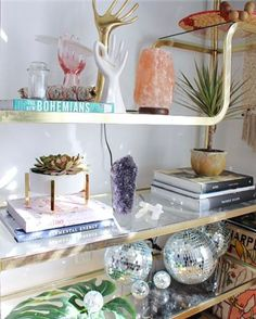 Mid century shelf styled with crystals, books, plants and disco balls.