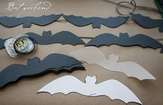 crafting resources already available through the Martha Stewart archives. found this simple bat pattern. sheet of vellum, cut one out to act as a template. Next, using poster board, cut out an entire colony.   Each bat was secured to a ribbon w/hot glue, which once dry, has found a new home against a mirror in dining room. Just cover each bat in glue and glitter