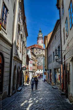 Main alley in the old town of Cesky Krumlov with its castle tower in the backround, Czech Republic by ilias nikoloulis