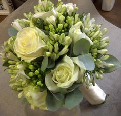 White bridal bouquet featuring roses, white agapanthus and bouvardia buds.