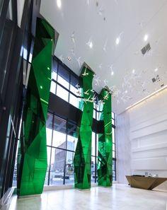 Toronto Condo Lobby uses Magilam custom green laminated shaped mirrors. #skylinedesign #torontomirror