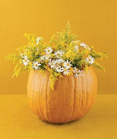 DIY Fall Centerpiece: Trim off its top of a pumpkin hollow out the seeds. Arrange fresh flowers in a water-filled jar and place inside, or use dried leaves and twigs.