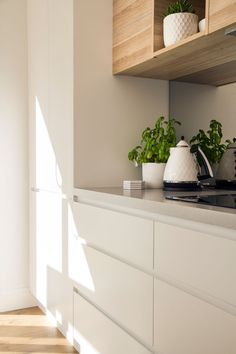 White handleless cabinetry + hint of timber