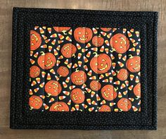 As you decorate for Halloween, dont forget to add a mug rug or two to your decor. This would look great on your coffee table, kitchen table or even on your desk at work. It is generously sized to hold your beverage of choice and a small snack. It is not only functional but also decorative. The pumpkins and candy corn are scattered onto a black background and then bordered and bound with a black and gold fabric. The back has another Halloween fabric in orange with flying bats which would…