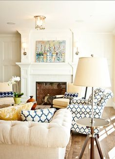 The living room is painted in a yellow with blue chairs, a linen chesterfield sofa, and a pair of yellow chairs by the fireplace.