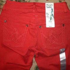 """Wrangler jeans in bright red with bling on pockets Brand new w tags, never been worn red Wrangler bootcut jeans in """"Sadie"""" style. They have an ultra low rise with a 34"""" inseam. Beautiful rhinestones border the pockets on the front and back, and embroidered designs beautify the back pockets. The triple lines on the sides of the back add a slimming, uplifting booty look! These are currently seen in stores at a much HIGHER price! Offers accepted and bundling available! Size 1. Wrangler Jeans"""