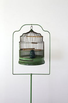 We had one quite similar to this, but I think ours dated from around the 1940's...Antique Birdcage with Stand // 1920s Green Bird Cage by 86home on Etsy...