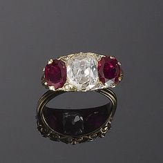 A late 19th century ruby and diamond three-stone ring, circa 1890 Centrally set with a cushion-shaped diamond between oval mixed-cut rubies with single and rose-cut diamond points