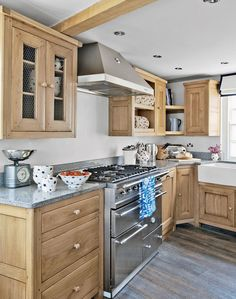 Mix elements of both modern and country for a smart yet cosy kitchen. Honey coloured oak cabinetry warms this compact space and has a timeless style. Rustic features like the butler sink and chicken wire cupboard contrast with modern stainless steel appliances, creating an eclectic mix.