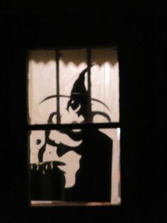 halloween characters cut out of poster board taped to windows then covered in tissue paper.