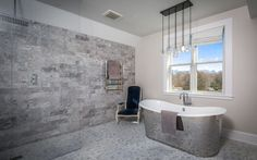 Bathe in luxury! Gorgeous private master bathroom furnished with polished mirrored steel tub and candle drop chandelier.