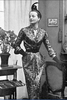 1949 Model in black lace over yellow gold cocktail dress, the straight skirt flares from hip pockets, by Robert Piguet, worn with black suede belt, gloves and matching hat