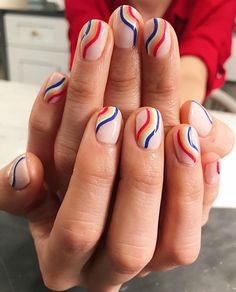 Nails in neutral pink with wavy colorful stripes design