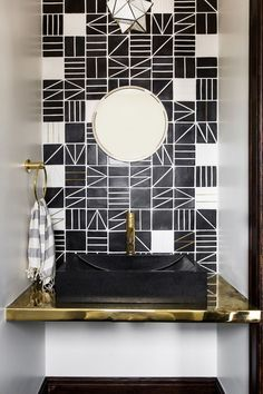 The powder room features a custom live-brass vanity set against an impressive tiled accent wall | archdigest.com