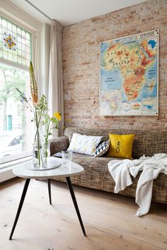Love the exposed brick, the stain glass window, and colours but not into the ant on the pillow!