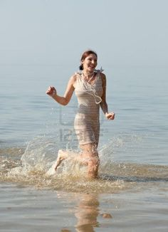 Woman in retro swimsuit smiles and runs through the water against the sea Stock Photo